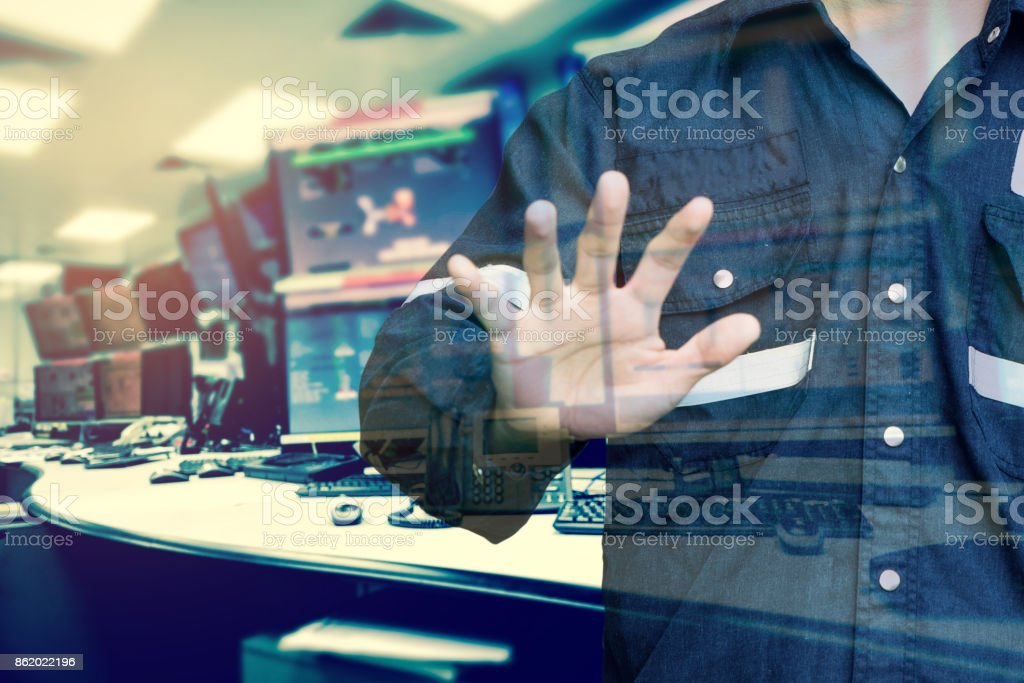 Double exposure of Engineer or Technician man  while using hand control monitor of computers room  for oil and gas industrial business concept. stock photo