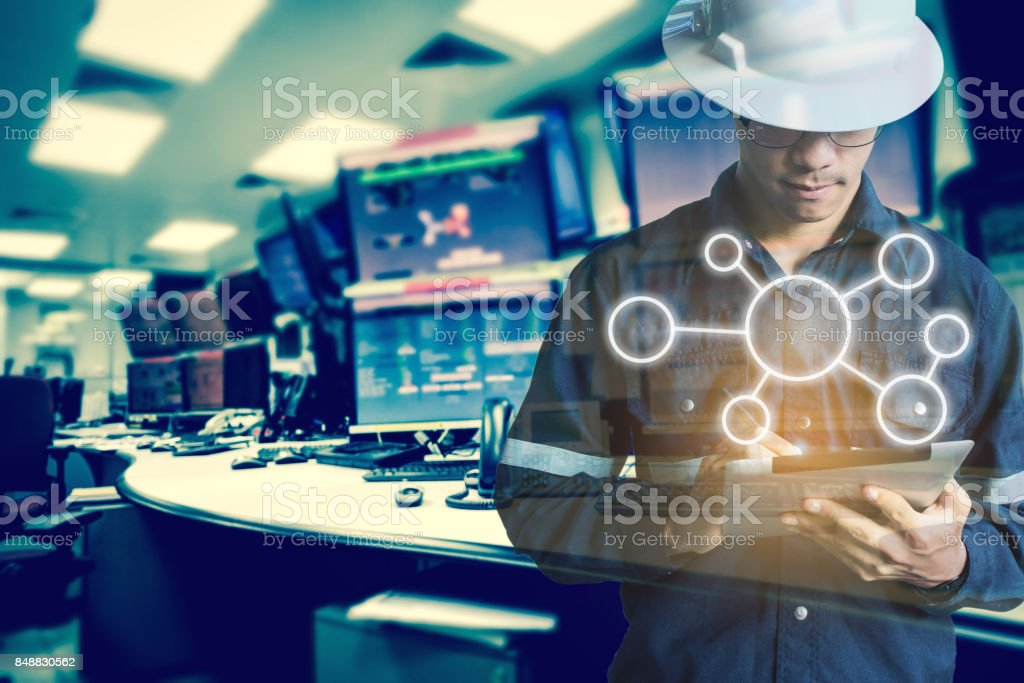 Double exposure of Engineer or Technician man with business industrial tool icons while using tablet with monitor of computers room  for oil and gas industrial business concept. stock photo