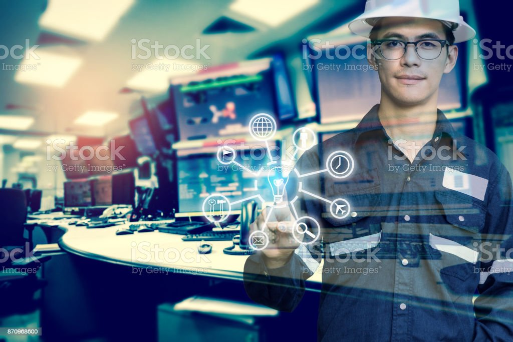 Double exposure of Engineer or Technician man with business industrial tool icons while pointing finger with monitor of computers room for oil and gas industrial business concept. stock photo