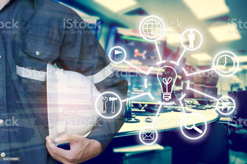 Double exposure of Engineer or Technician man with business industrial tool icons holding safety hat with monitor of computers room  for oil and gas industrial business concept. stock photo