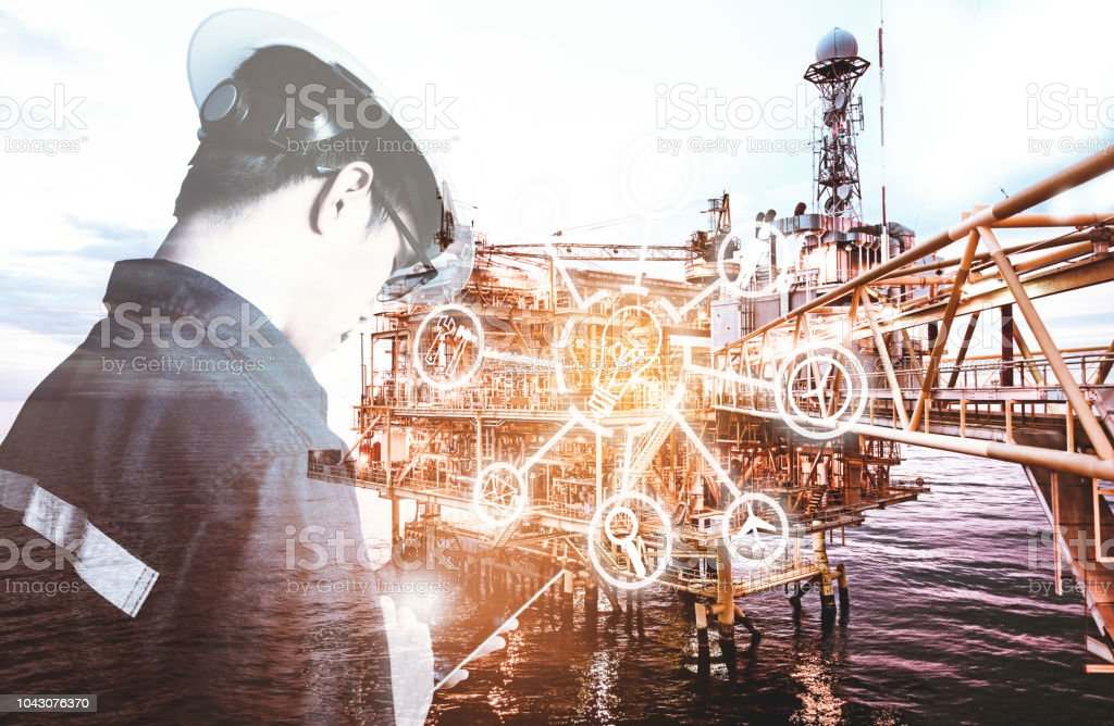 Double exposure of Engineer or Technician man with digital icon operated platform or plant by using tablet with offshore oil and gas platform background for industry business concept. stock photo