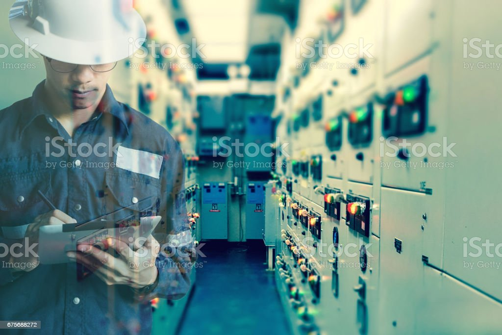 Double exposure of  Engineer or Technician man working with tablet in switch gear electrical room of oil and gas platform or plant industrial for monitor process, business and industry concept royalty-free stock photo