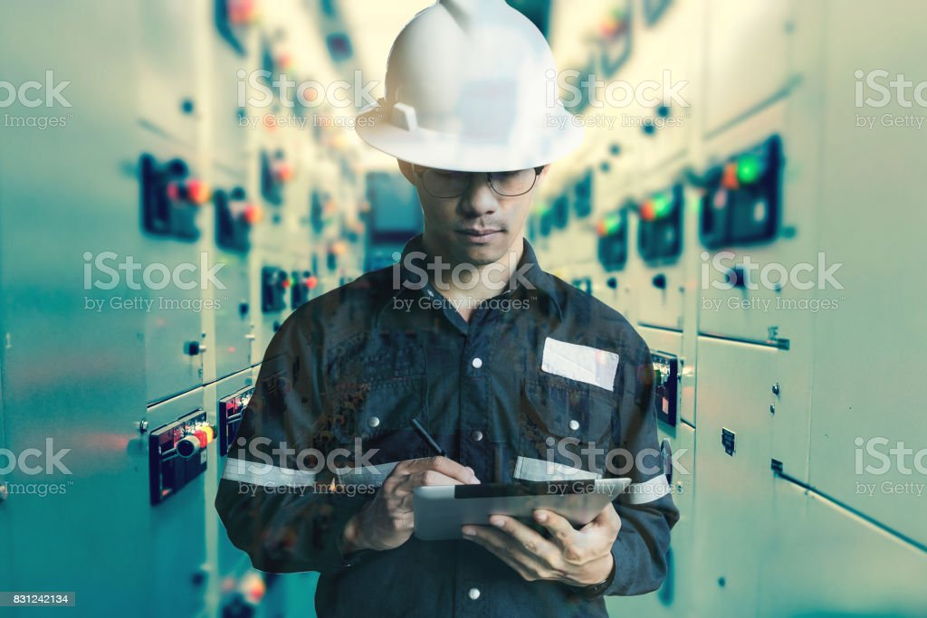 Double exposure of  Engineer or Technician man working with tablet in switch gear electrical room of oil and gas platform or plant industrial for monitor process, business and industry concept. stock photo
