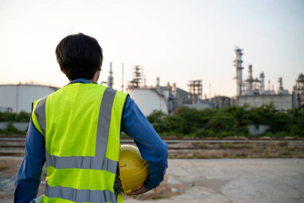 Double exposure of Engineer with safety helmet with oil refinery industry plant background stock photo