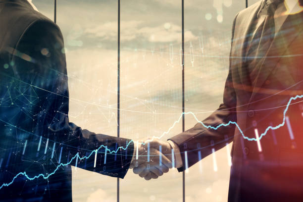 Double exposure of forex graph hologram and handshake of two men. Stock market concept. stock photo