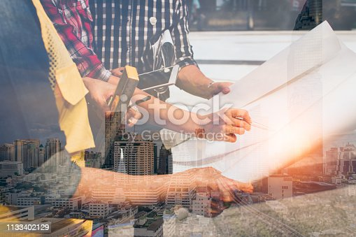 istock Double exposure of hand engineer with modern city background.meeting for architectural project working with partner and engineering tools on workplace. 1133402129