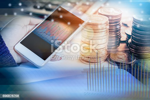 istock double exposure of hand holding smart phone with financial graph, stack of coins 696828258