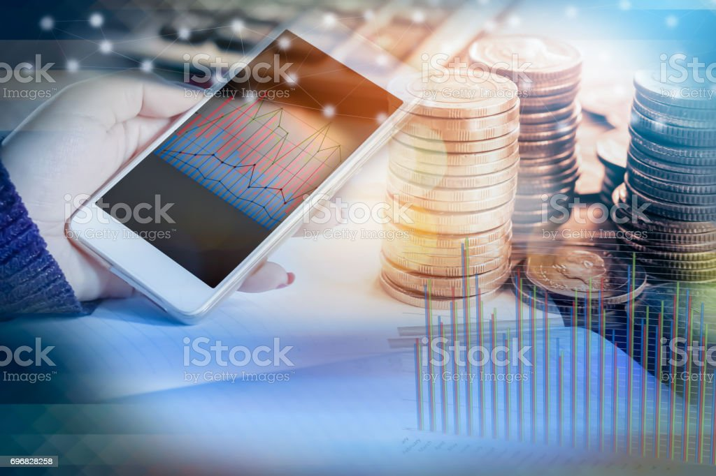 double exposure of hand holding smart phone with financial graph, stack of coins stock photo