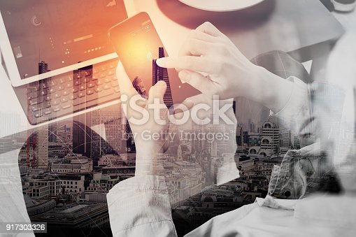 istock Double exposure of hand using smart phone and digital tablet computer for online banking payment communication in modern office with London city 917303326