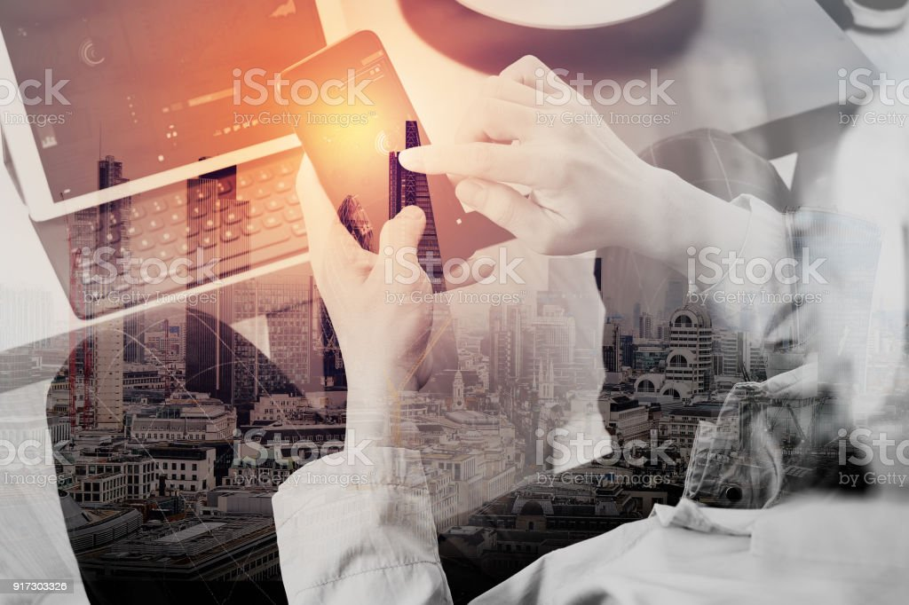 Double exposure of hand using smart phone and digital tablet computer for online banking payment communication in modern office with London city stock photo