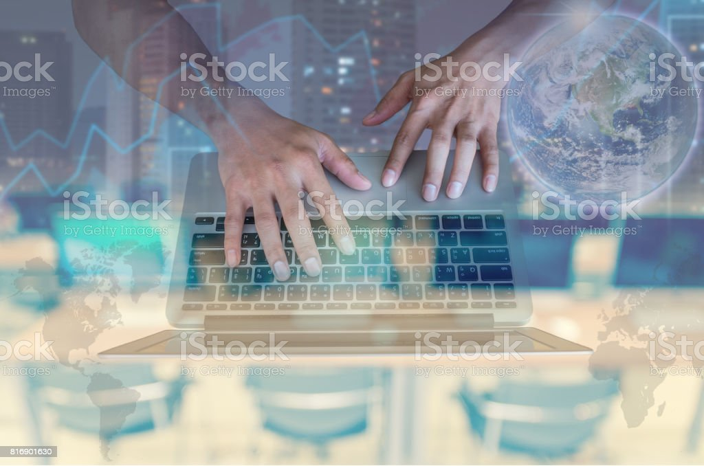 Double exposure of hand using the laptop with cityscape and financial graph on computer blurred background, Elements of this image furnished by NASA, education and business concept stock photo