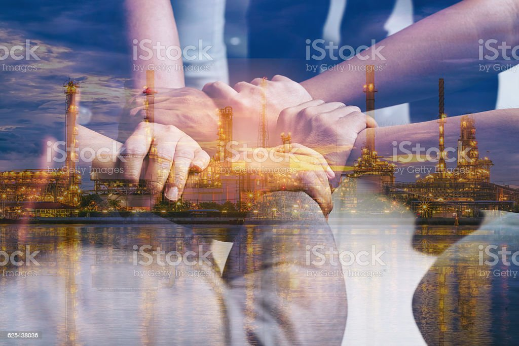 Double exposure of hands collaboration and oil refinery stock photo
