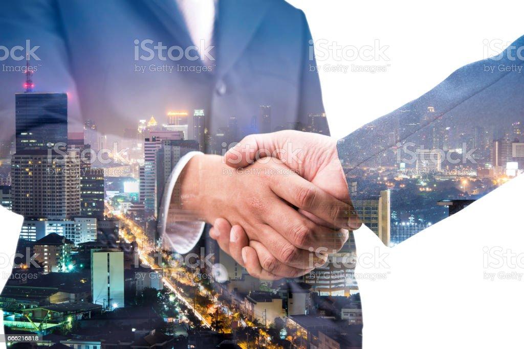 Double exposure of handshake and city night stock photo