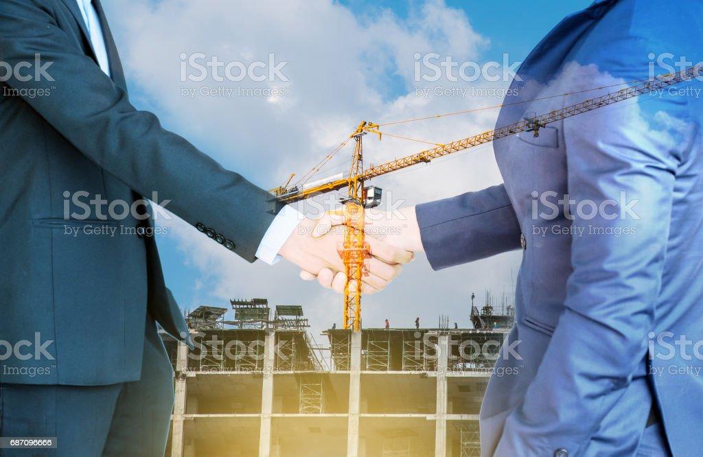 Doppelbelichtung Handshake und Bauwesen Hintergrund Lizenzfreies stock-foto
