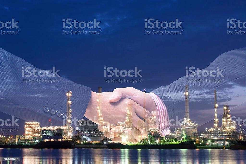 Double exposure of handshake and refinery plant stock photo