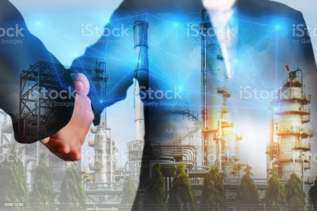 Double exposure of handshake, digital light networking world map, Electric Generating, fuel oil Factory and Energy Industry plant at sunset as business, commitment, teamwork and industrial concept. stock photo