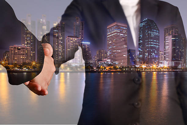 二重照射の握手夜の街、都会と湖 ストックフォト