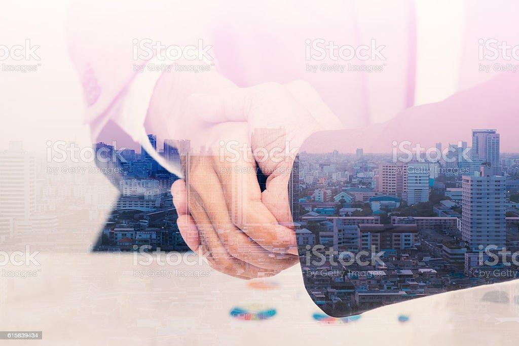 Double exposure of handshake with citi background stock photo