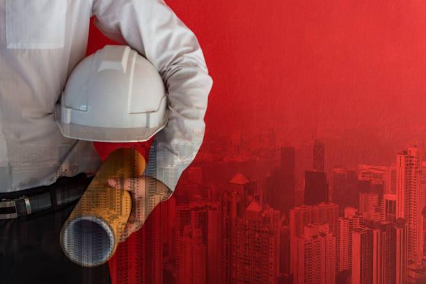 Doppelte Belichtung des männlichen Bauingenieurs mit Schutzschutzhelm und architektonischer Zeichnung in der Nähe von rotem Betonwand mit dem Hintergrund der Stadt Hongkong. Architekturdesign und Baugewerbe – Foto
