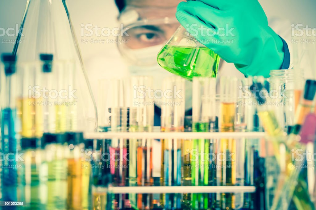 Double exposure of man scientist looking at green chemical solution...