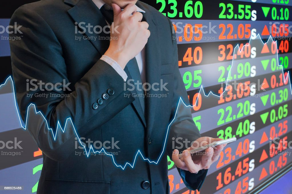Double exposure of professional businessman thinking and look at smart phone with cityscape and financial / trading graph in Business trading and technology concept foto stock royalty-free