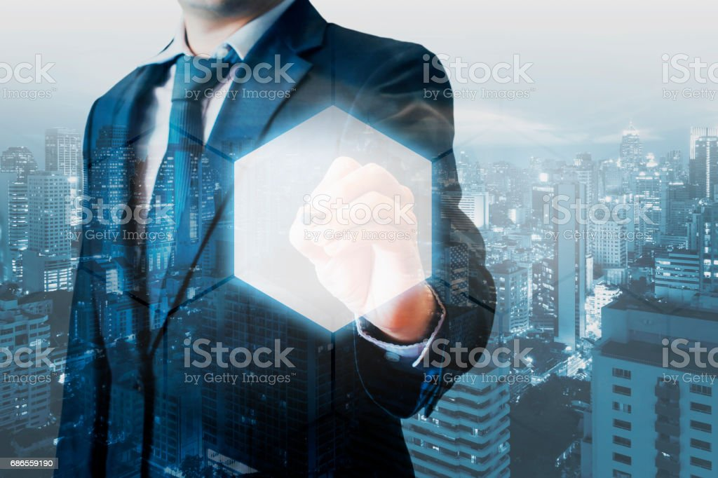 Double exposure of professional businessman touching hexagonal polygon button on a digital interface and city of business background in business and technology choices concept foto stock royalty-free