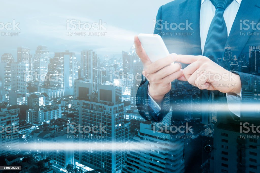 Double exposure of professional businessman using smart phone and network connection with city of business background in communication & Business trading concept royalty-free stock photo