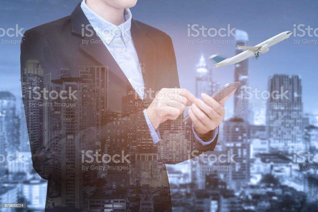 Double exposition de femmes d'affaires intelligent utiliser smartphone pour la réservation de billet d'avion avec vue sur la ville intelligente. photo libre de droits