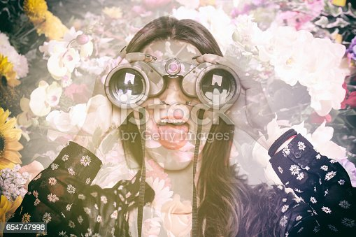 istock Double exposure of surprised girl looking through binoculars and flowers 654747998