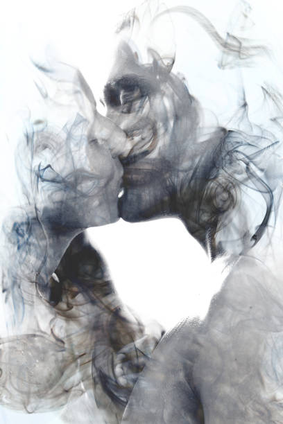 Double exposure of two blissful people close up embracing and becoming one with the smoky texture, black and white stock photo