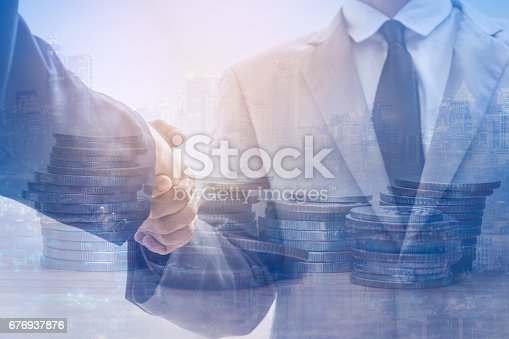 istock Double exposure of Two business people handshake and coins 676937876