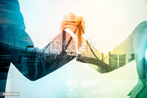 istock Double exposure of two business persons shaking hands and bridge skyline, relationship conceptual abstract 684807600