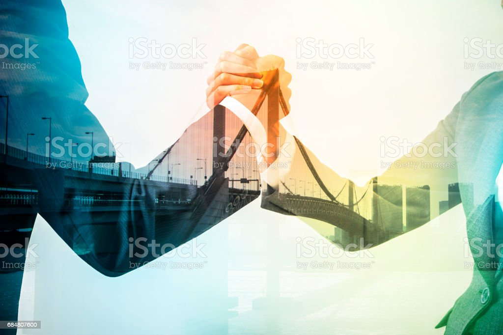 Double exposure of two business persons shaking hands and bridge skyline, relationship conceptual abstract - foto stock