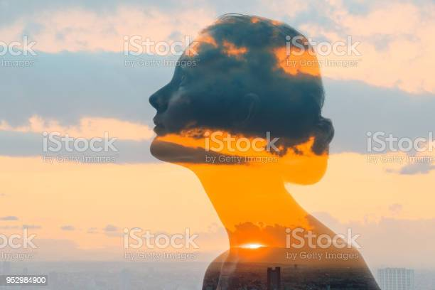 Photo of Double exposure of woman face and sunset glow.