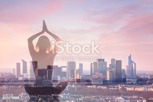 istock Double exposure of woman practicing yoga and city background 512476868