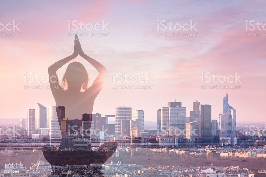 Double exposure of woman practicing yoga and city background stock photo