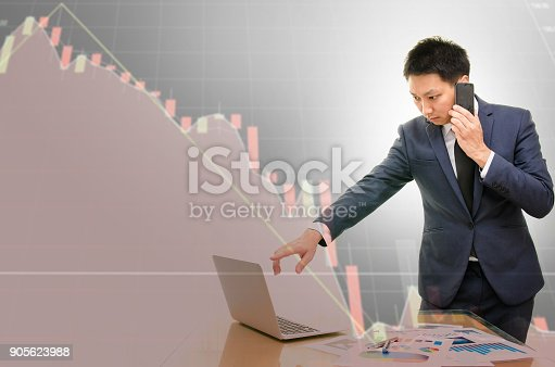 istock Double exposure of young businessman talking on the phone with stress and the technical chart of stock losses in background. 905623988