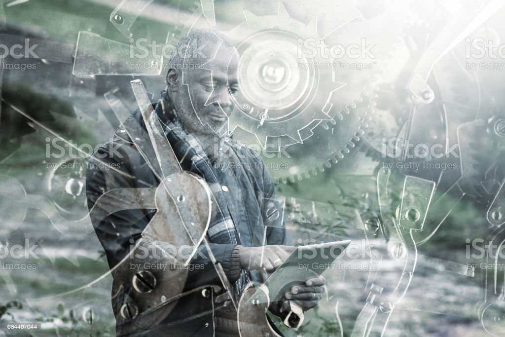 Double exposure photo of a black man with tablet and gears stock photo