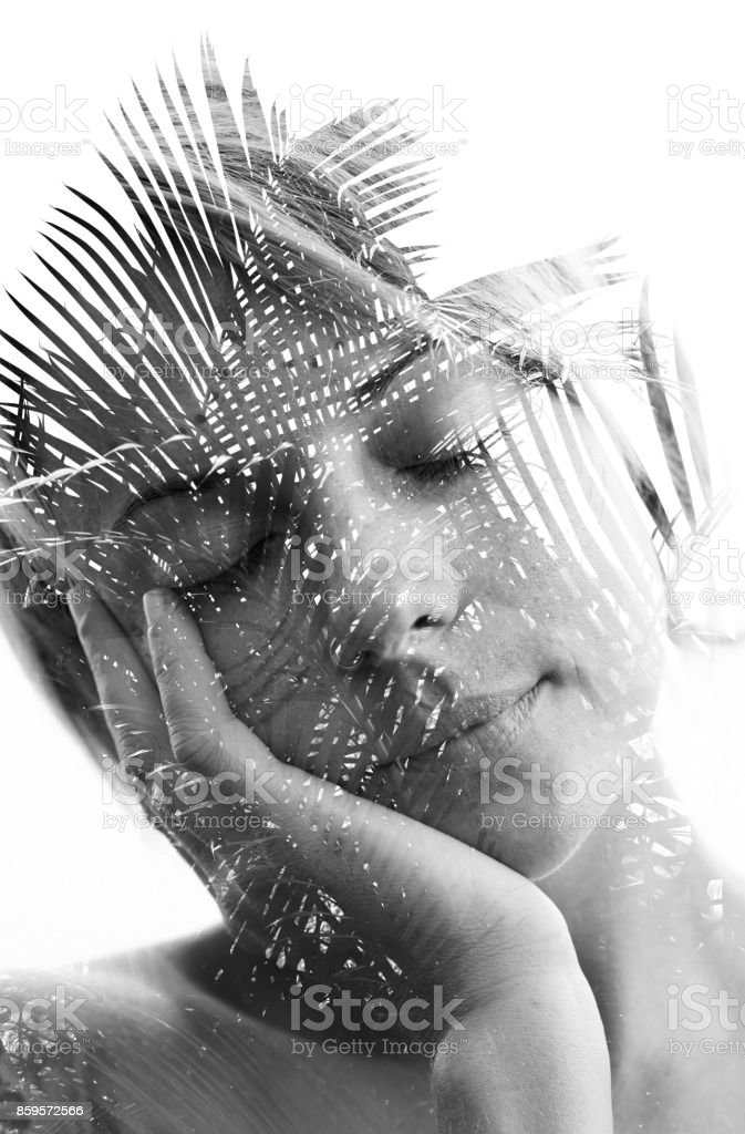 Double exposure portrait of a naturally beautiful girl in a dream-like state combined with branches of a palm tree stock photo