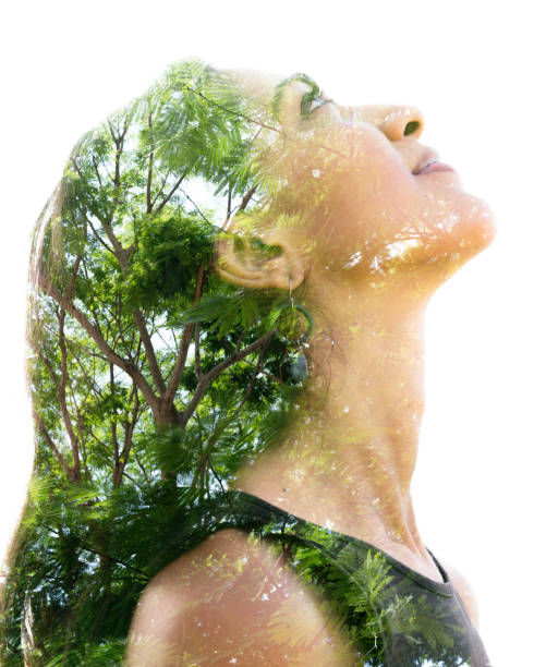Double exposure portrait of a naturally beautiful happy woman and a tree with bright green leaves stock photo