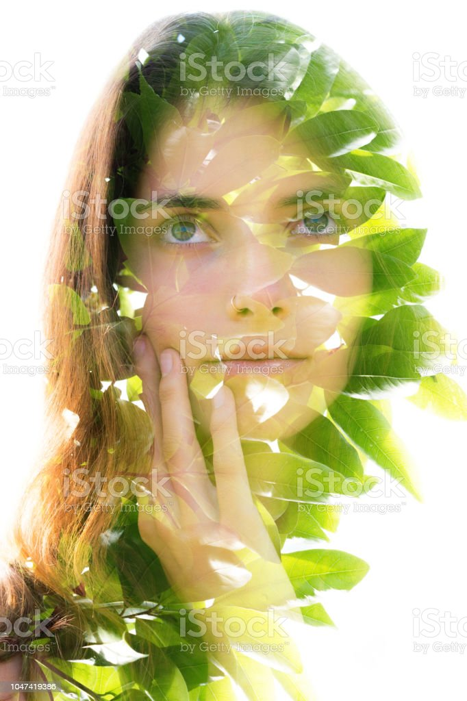 Double exposure portrait of a naturally beautiful woman softly touching her face and bright green tropical leaves stock photo