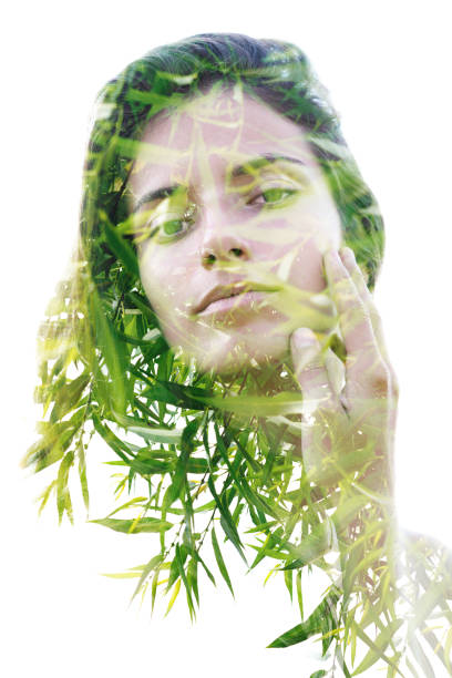 Double exposure portrait of a naturally beautiful woman softly touching her face combined with bright leaves of a bamboo plant stock photo