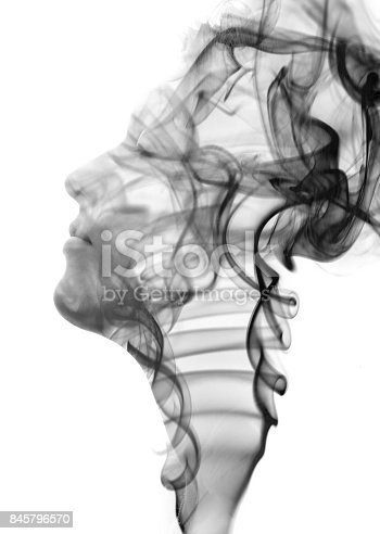 istock Double exposure portrait of a sensual model dissolving into a rising pattern of smoke in black and white 845796570