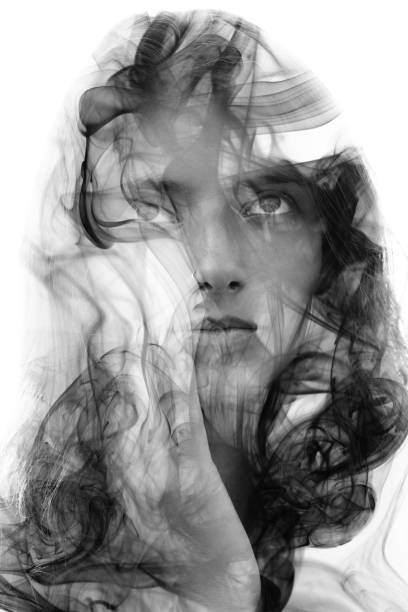 Double exposure portrait of a sensual model gently touching her face combined with a photography of smoke stock photo