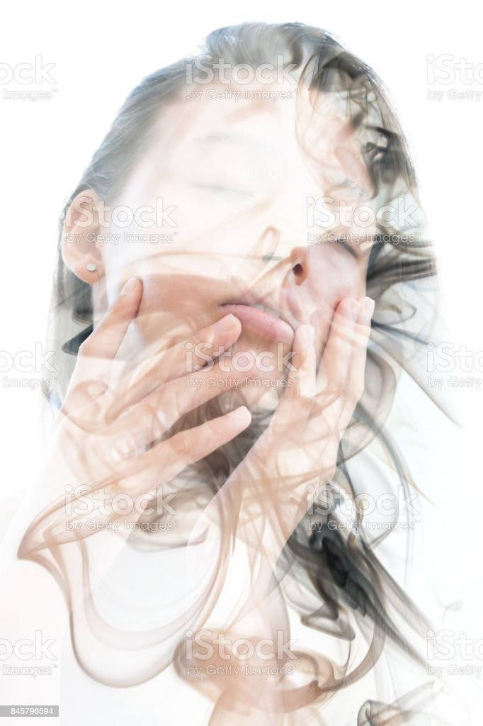 Double exposure portrait of a sensual model gently touching her face and a smoky texture'n'n stock photo
