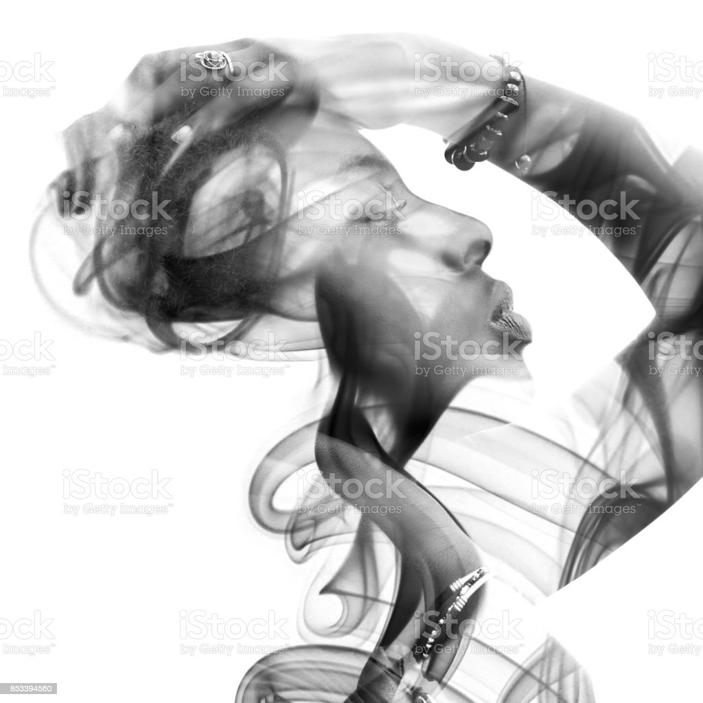 Double exposure portrait of a sexy dark skinned woman and a smoky texture interweaving seamlessly stock photo
