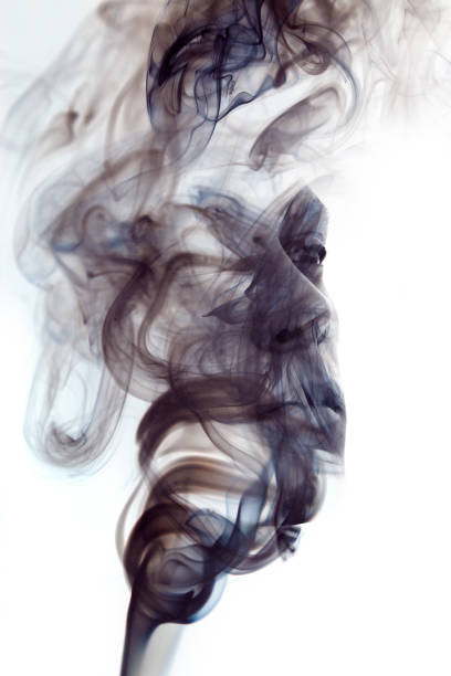 Double exposure portrait of a sexy man with dark features hiding behind a curtain of smoke stock photo