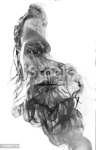 istock Double exposure portrait of a sexy man with dark features hiding behind a curtain of smoke