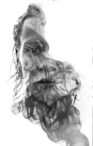 Double exposure portrait of a sexy man with dark features hiding behind a curtain of smoke