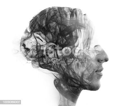 istock Double exposure portrait of a sexy statuesque man with dark features blending into a curtain of smoke 1009086002